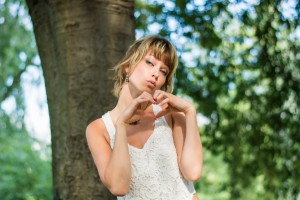 Pretty blonde young woman doing heart sign with hands
